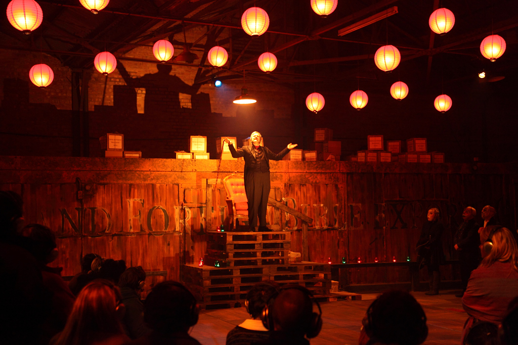 a man in a play talks to the audience in a warehouse