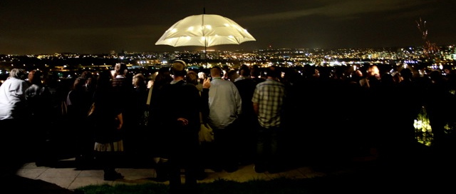an audience stands outside under an illuminated umbrella