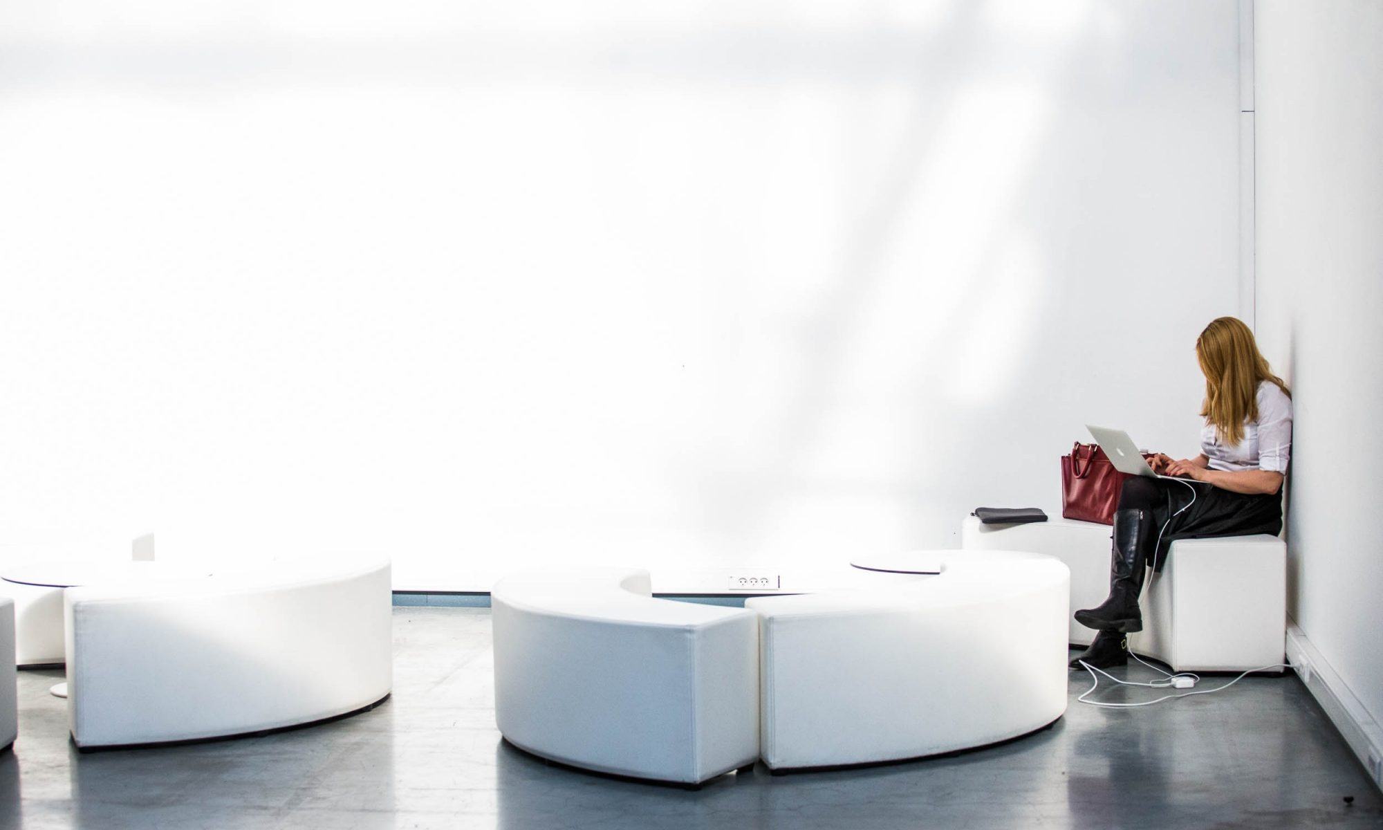 A woman works on a laptop in the corner of a pristine white office foyer