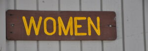 The word 'women' painted in yellow on a wooden board