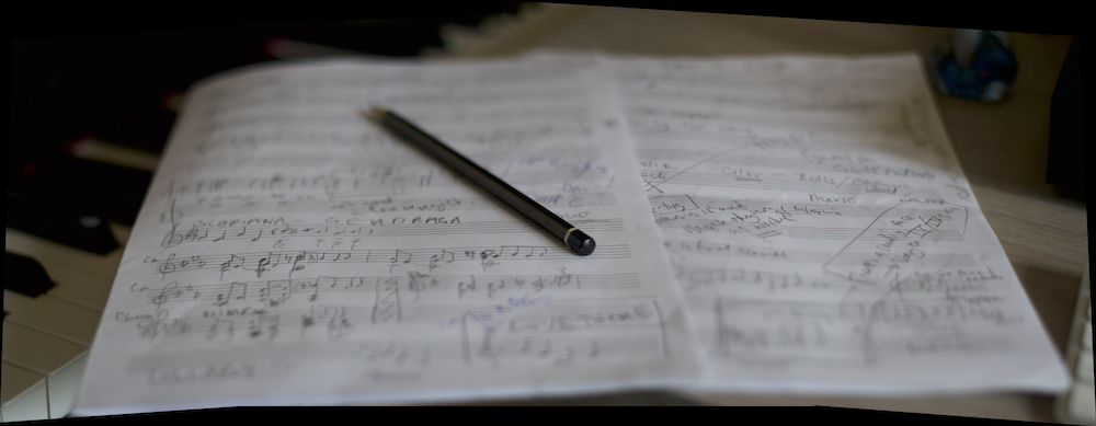 A pencil rests on a piece of manuscript paper with scribbled music notes, by piano keys