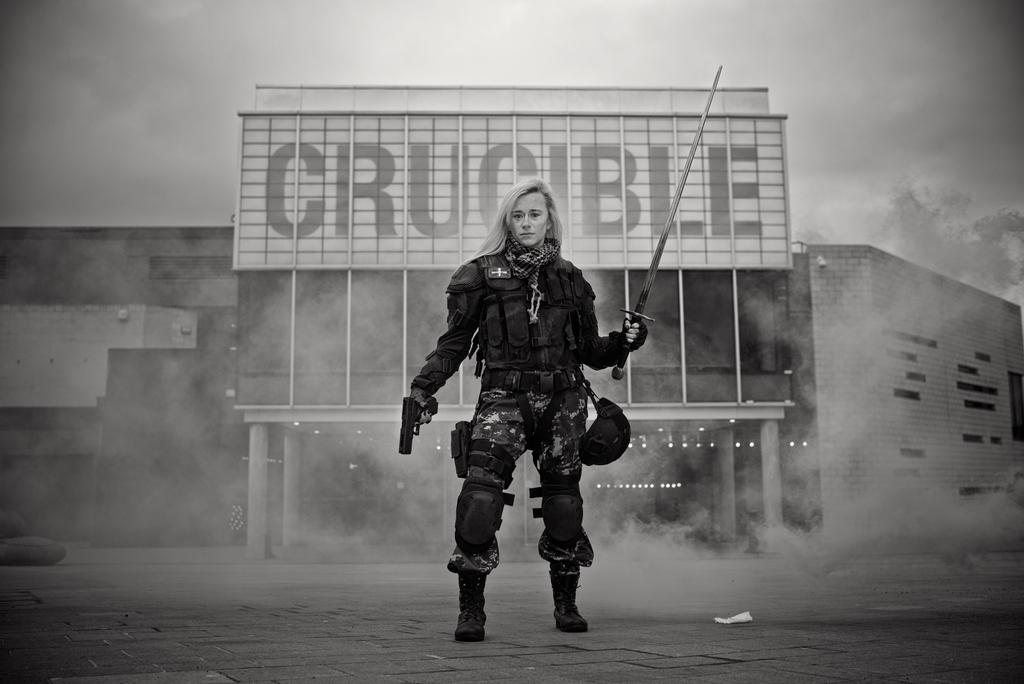Promotional Image from Camelot: The Shining City, where Bear holds a sword and a gun outside the Crucible Theatre